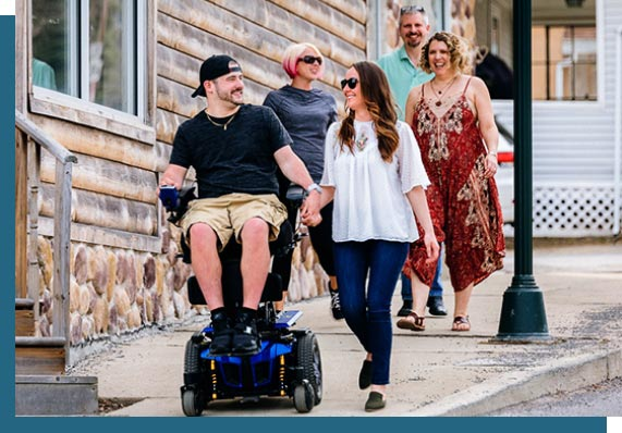 man walking with woman while seated in wheelchair