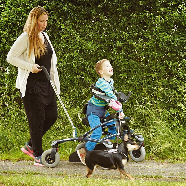Boy and mother walking while using the The Etac/R82 Mustang pediatric folding gait trainer