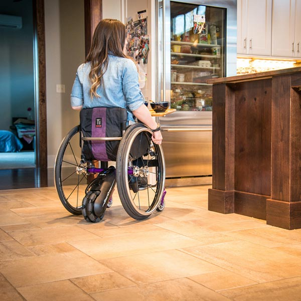 Max Mobility SmartDrive MX2 Wheelchair Power Assist being used by girl in kitchen setting