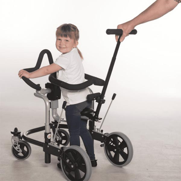girl child using pediatric Meywalk 4 with parent holding onto safety handlebar guiding the child