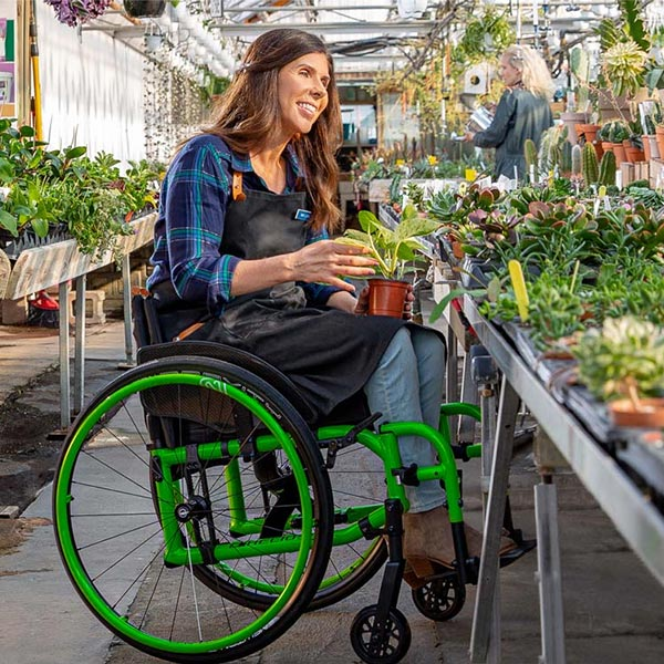 woman holding flower while riding in Motion Composites Helio A7 Lightweight Folding Wheelchair