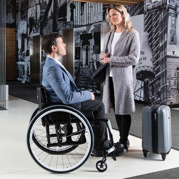 man in Motion Composites Veloce Lightweight Folding Wheelchair talking with standing woman