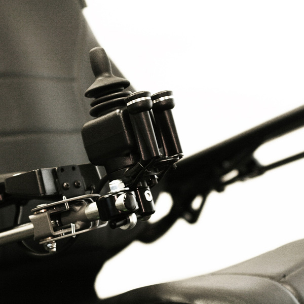 Close-up shot of the Permobil Compact Joystick, black rubber wheelchair control joystick from the left-side perspective