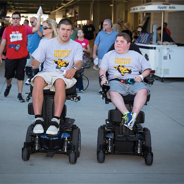 One man and one boy using the J6 Jazzy power wheelchair at a baseball game