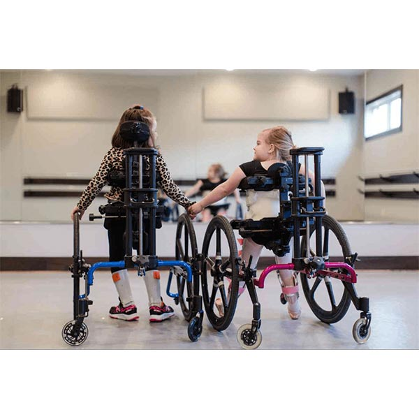 two female children embracing in a dance class in their Prime Engineering KidWalk Pediatric Gait Trainers