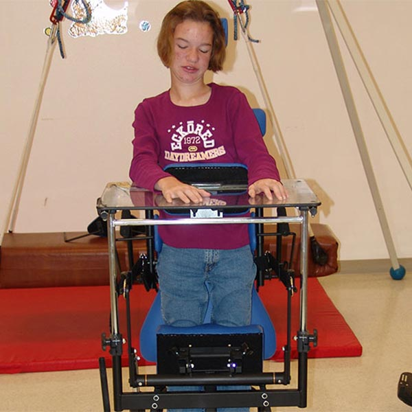 Teenage girl using the Prime Engineering Symmetry Youth Pediatric Standing Frame with the desk attachment