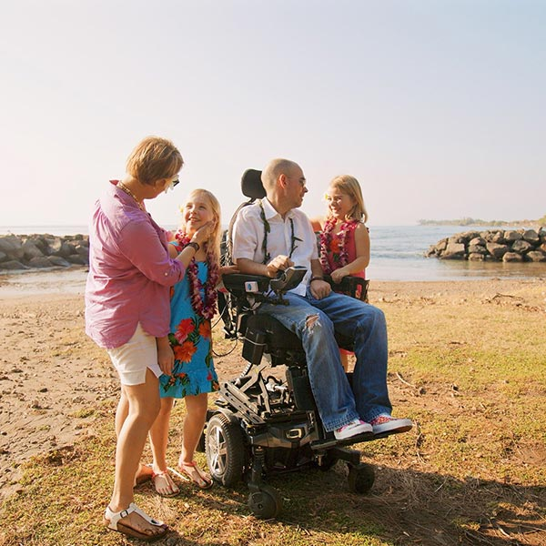 man on beach with family seated in a power wheelchair using the Quantum Q6 Edge 2.0