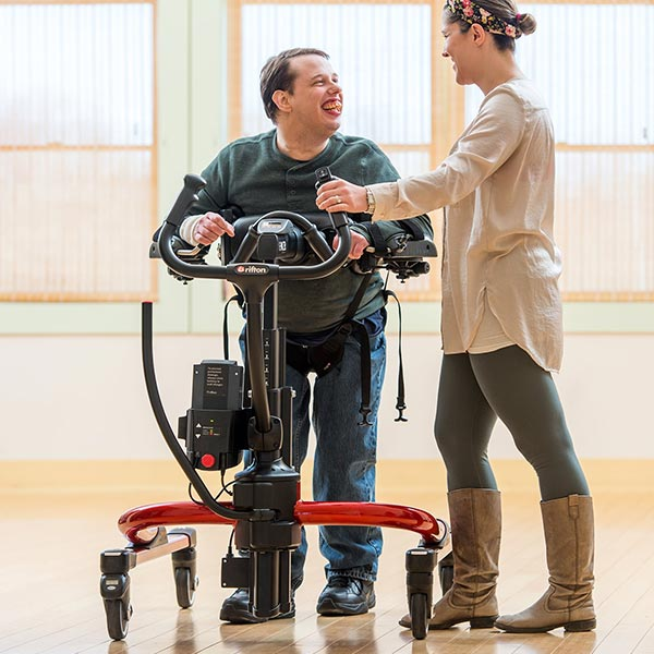 Adult male using the Rifton E-Pacer Adult Gait Trainer working with female caregiver